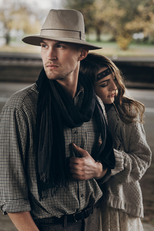stylish hipster couple gently hugging. boho woman touching arm of confident man in hat under abandoned bridge. atmospheric sensual moment. rustic fashionable look.