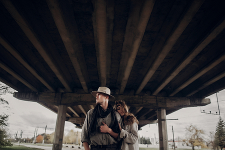 stylish hipster couple. boho gypsy woman gently hugging arm of confident man in hat under abandoned bridge. atmospheric sensual moment. rustic fashionable look. Stock Photo
