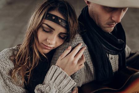 Romantisch donkerbruin hipstermeisje in bohokleren die knappe cowboymusicus koesteren met gitaar en een sjaalclose-up Stockfoto