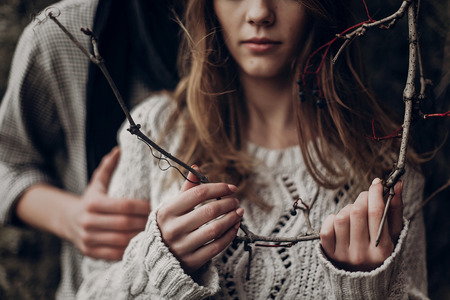Tender beautiful hipster woman in white sweater holding black berry branch, hands closeup Stock fotó
