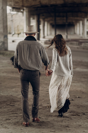 Handsome texas cowboy man in white hat holding hands with beautiful gypsy woman in white dress, couple walking in the city