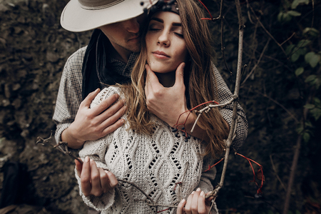 stylish hipster couple tender hugging. boho gypsy woman holding branch and man in hat embracing her. atmospheric sensual moment. rustic fashionable look. Stock Photo