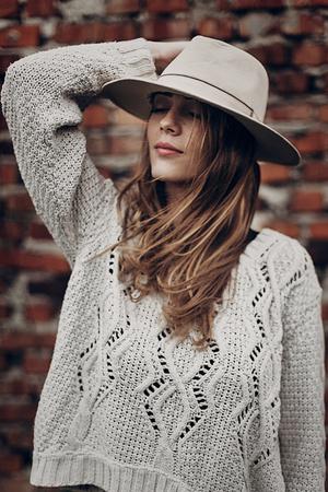 세련 된 힙합 여자 모자를 들고 벽돌 벽의 배경에 니트 스웨터에서 포즈. 대기 관능적 인 순간. boho 나라 유행 봐. 자유로운 사람들