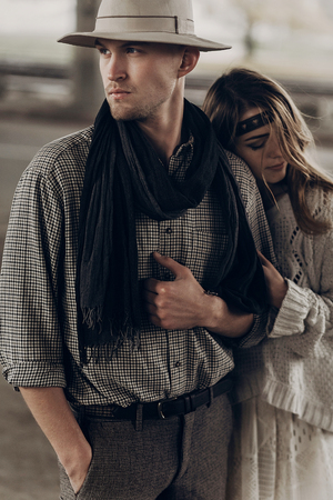 Romantic gypsy woman in stylish boho clothes and white dress hugging handsome cowboy man in white hat and scarf Stock Photo