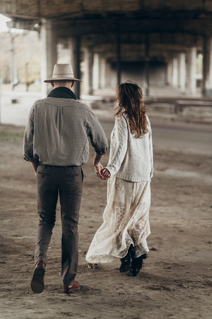 stylish hipster couple walking and holding hands. man in hat and boho woman in knitted sweater under abandoned bridge . atmospheric sensual moment. rustic fashionable look.