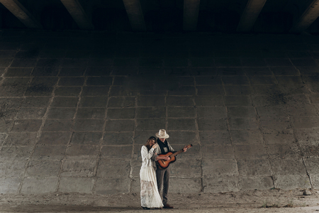 stylish hipster couple hugging under bridge. man in hat playing guitar for his boho woman in knitted sweater. atmospheric sensual moment. rustic fashionable look. Stock Photo