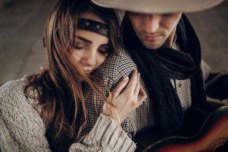 Romantic brunette hipster girl in boho clothes hugging handsome cowboy musician with guitar and a scarf closeup Stock fotó