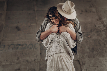 Handsome stylish cowboy man in hat and shirt embracing beautiful gypsu woman from behind, sensual couple smiling
