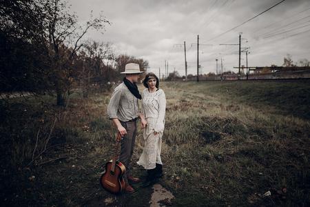세련 된, 관능적 인 hipster 몇 boho 옷, 잘 생긴 뮤지션 남자와 집시 철도 트랙 근처가 필드에 손을 잡고