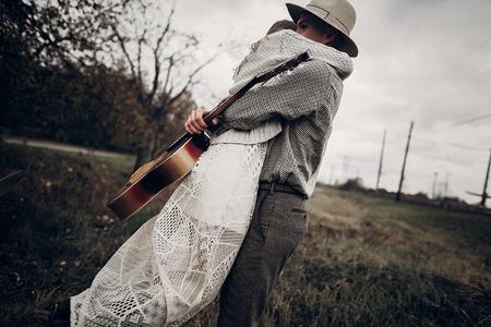 세련 된 hipster 몇 포옹 필드, 잘 생긴 카우보이 음악가 기타와 인디 스타일 여자 흰색 스웨터에서 기차역 근처 포즈