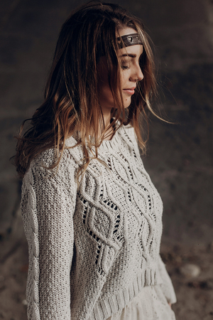 Stylish brunette hipster girl posing outdoors in knitted sweater