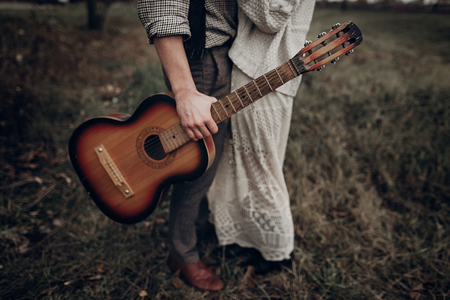 stylish hipster couple posing in windy field. boho gypsy woman and man with guitar in windy field. atmospheric motion moment. fashionable look. rustic wedding concept