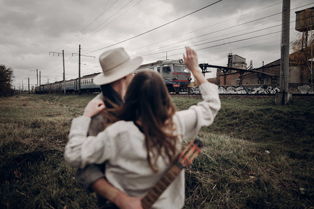 관능적 인 힙합 커플, boho 옷을 입은 집시 여성, 기차를 지나칠 때 기타가있는 음악가