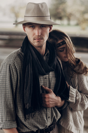 Handsome cowboy  man with a white hat and black scarf in a stylish shirt being hugged by beautiful indie woman, seductive look