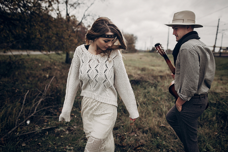 Romantic hipster couple, handsome musician man with guitar and gypsy woman in boho sweater dancing in autumn field Reklamní fotografie