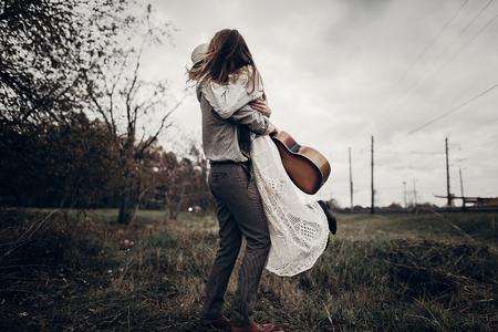 stijlvolle hipster paar dansen in winderige veld. boho zigeunervrouw en man in hoed omarmen in winderige veld. atmosferisch bewegingsmoment. modieuze look. rustieke bruiloft concept