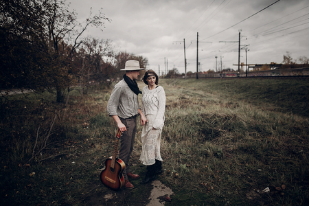 Stylish, sensual hipster couple in boho clothes, handsome musician man and gypsy girl holding hands in autumn field near railway track