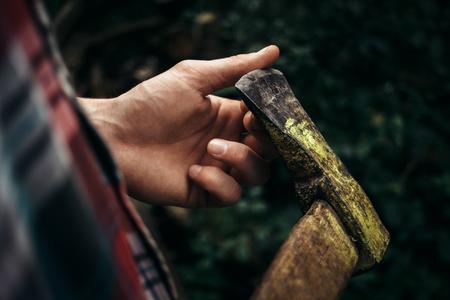 stijlvolle hipster houthakker met bijl in het zonnige bos in de bergen