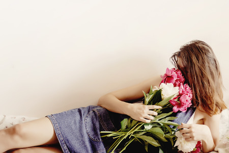 happy woman hipster  smelling peony bouquet lying on bed in the morning, sweet romantic moment , space for text