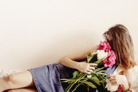 Hipster de mujer feliz que huele el ramo de peonía acostado en la cama por la mañana, momento romántico dulce, espacio para texto Foto de archivo - 75305869