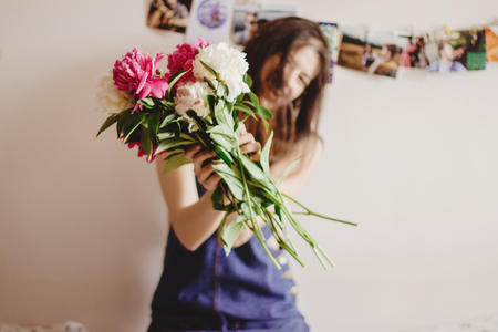 happy woman hipster  holding peony bouquet in front of face and smiling in the morning, sweet romantic moment , space for text
