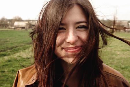 stijlvolle mooie brunette meisje lopend en smilling buitenshuis in voorjaar portret