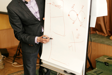 faculty: elegant speaker lecturer drawing charts at white board, at meeting, business marketing lecture coaching Stock Photo