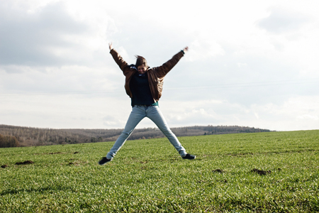 stylish beautiful brunette girl hipster jumpinh and having fun outdoors in spring field