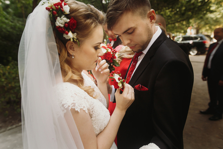 Beautiful bride putting on boutonniere on groom, blonde bride in white wedding dress and veil pinning flowers on grooms black suit closeup