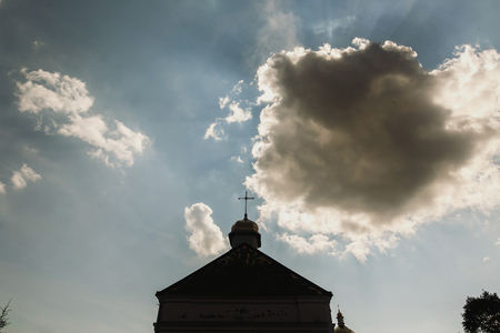 Top of christian church, golden cross on top of orthodox chapel, blue skies and white clouds in background Stock Photo