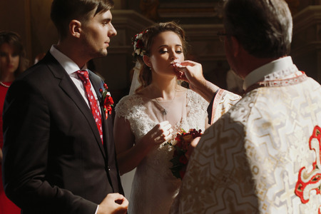 Beautiful bride and handsome groom kissing wedding rings, spiritual christian couple kissing gold rings during wedding ceremony in church, romantic moment Stock Photo