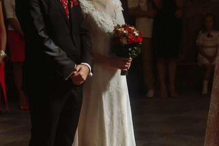 Spiritual couple, handsome groom in stylish suit and bride in vintage white dress with bouquet standing in church during wedding ceremony, hands closeup