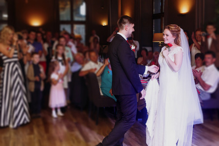 Romantic bride and groom dancing and holding hands at wedding reception in restaurante, newlywed couple first dance at evening party, guests looking in the background