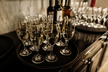 luxury glasses with golden champagne on stylish decorated table at wedding reception. expensive catering at restaurant for celebrations. transparent glass and space for text. alcohol bar