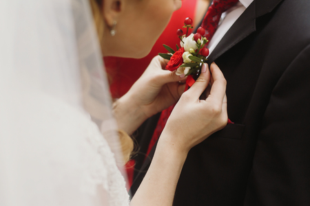 gorgeous bride putting on boutonniere on stylish groom suit at wedding morning ceremony. fashionable red flowers . romantic moment