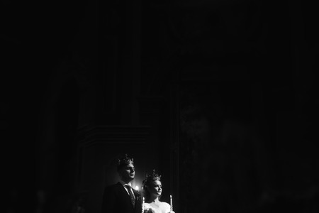 wedding ceremony at church. stylish groom and bride holding candles and giving vows. spiritual  sensual moment. space for text. black white photo