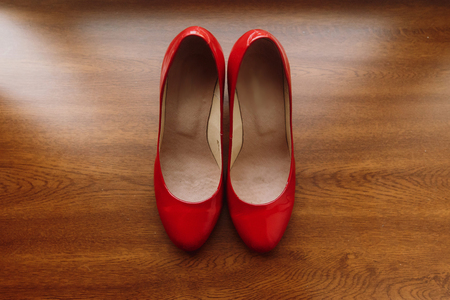 Stylish red women's shoes on wooden floor, elegant bride's shoes closeup on rustic background, morning wedding preparation