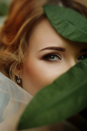 amazing bride portrait with green leaves and sensual eye look. elegant woman with gorgeous make up and green floral in city street. wedding day. romantic moment