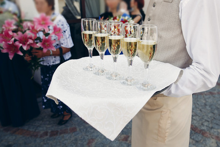 Elegante geklede ober bedrijf dienblad met champagne in glazen bij huwelijksreceptie in luxe restaurant, catering concept