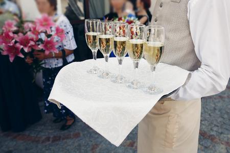 Elegante vestido camarero bandeja con champán en vasos en la recepción de la boda en el restaurante de lujo, catering concepto Foto de archivo - 75615939