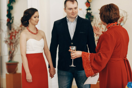 Mother in law pronouncing toast to happy newlywed couple, woman with champagne glass drinking to bride and groom at wedding ceremony in registry office