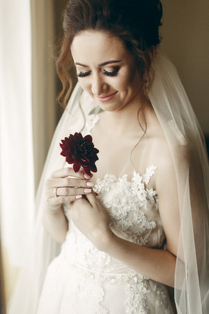 portait: Gorgeous bride in vintage lace white wedding dress holding red flower, portait of beautiful woman posing near a window, wedding concept Stock Photo
