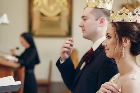 Sensual happy bride and groom wearing gold crowns during wedding ceremony in christian church, coronation ritual indoors face close-up, marriage concept