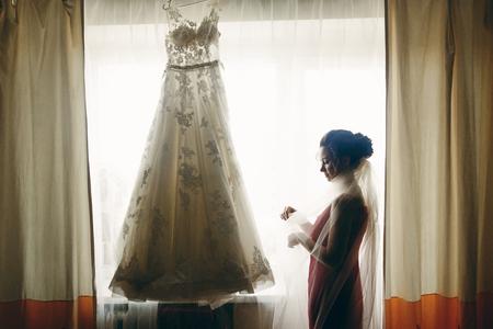 Schitterende donkerbruine bruid die met sluier uitstekende witte huwelijkskleding bekijken die op het venster, de voorbereiding van het ochtendhuwelijk, huwelijksconcept hangen