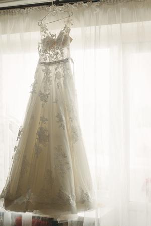 Mooie witte trouwjurk opknoping in de buurt van een raam in de hotelkamer, ochtend bruiloft voorbereiding, witte kanten jurk voor bruid op hanger Stockfoto