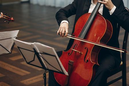 Légant quatuor à cordes effectuant à la réception de mariage au restaurant, bel homme en costumes jouant du violon et violoncelle au théâtre jouer close-up d'orchestre, concept de musique Banque d'images - 75727469