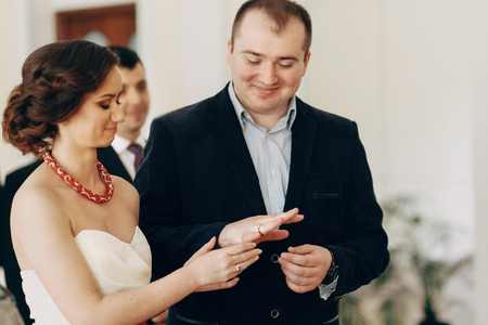 registro: Beautiful wedding ceremony moment, handsome groom exchanging golden wedding rings with beautiful bride at registry office, marriage concept