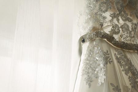 Mooie witte trouwjurk opknoping in de buurt van een raam in de hotelkamer, ochtend bruiloft voorbereiding, witte kanten jurk voor bruid op hanger close-up