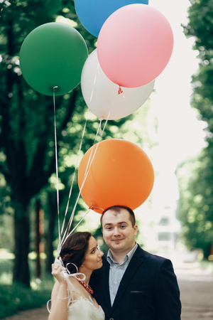 Happy family portrait, newlywed couple hugging in a sunny park in the summer, handsome groom looking at happy bride with balloons, funny couple posing