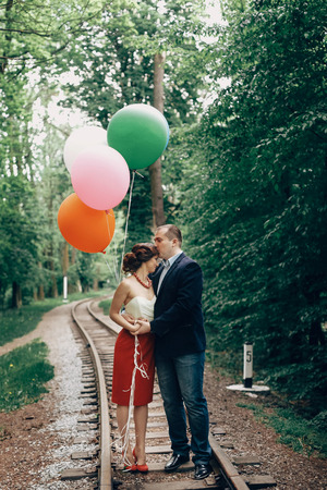 Beautiful portrait of fun newlywed couple with balloons, handsome groom kissing bride on forehead near old railway in a park, travel concept Stock Photo